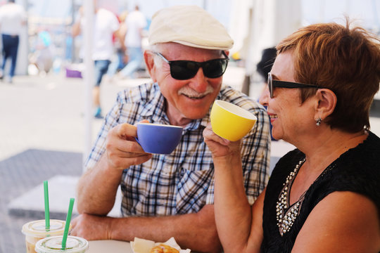 Portrait of senior couple sitting in summer cafe