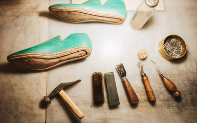 Shoes and instruments on table at footwear workshop.