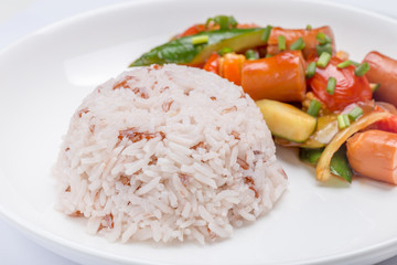 Close-up stream brown rice with blurred background of fried sausages and mixed vegetables in ketchup sauce, healthy eating concept.