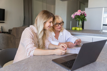 Smiling granddaughter and her grandmother shopping online