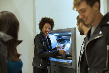 Young woman out at night with friends taking cash with credit card from cash point