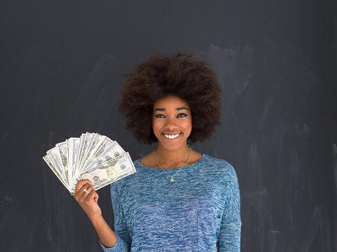 black woman holding money on gray background