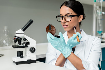 Attractive female scientist in eyeglasses applying makeup while working with microscope in lab