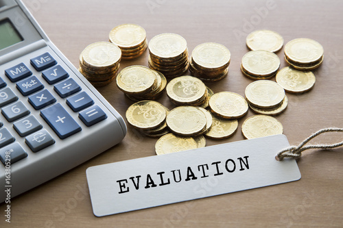 Evaluation Word On Tag Label With Calculator And Gold Coins Financial Concept