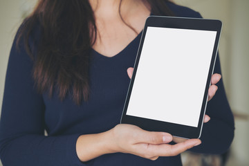 Mockup image of a business woman holding and showing black tablet with blank white screen in office