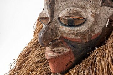 Hand made African mask with ropes simulating hair. Human face. Isolated on white background.