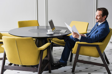 Happy male manager working with papers in cozy office