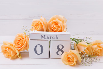 Peach color roses flowers and  calendar on white wooden planks.