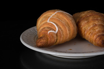 Cinnamon crescents croissant on white plate on black background