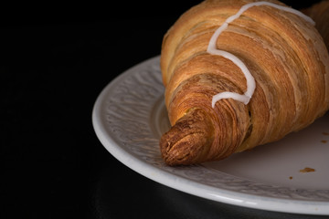 Cinnamon crescent croissant close up view on white plate on black background