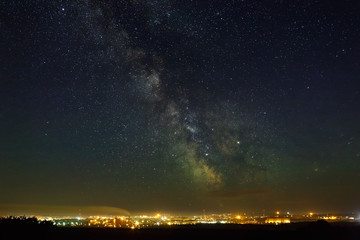 Starry night sky with the Milky Way over the city with lighting.