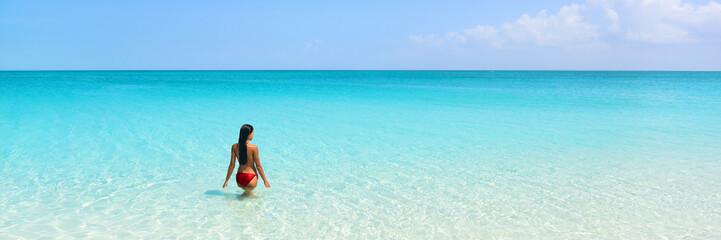 Wall Mural - Beach luxury travel getaway resort vacation banner. Bikini woman relaxing enjoying tropical holidays swimming in turquoise ocean water in paradise destination.