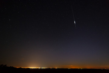 A bright meteorite on the night starry sky.