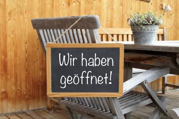 Holzstuhl mit Tafel: Wir haben geöffnet