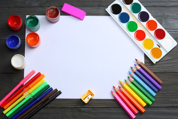 school and office supplies. school background. colored pencils, pen, pains, paper for  school and student education on dark wooden background. top view with copy space
