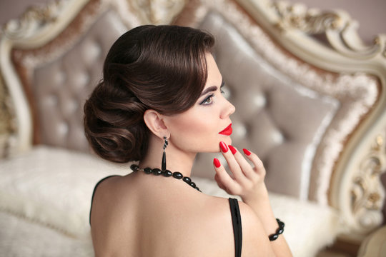 Retro brunette with red lips hollywood makeup, fashion jewelry, wavy hairstyle. Elegant woman in black sexy dress posing on modern sofa in luxury interior.