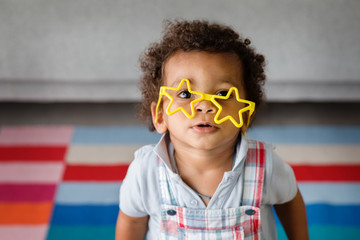 portrait of toddler boy wearing crooked star-shaped glasses