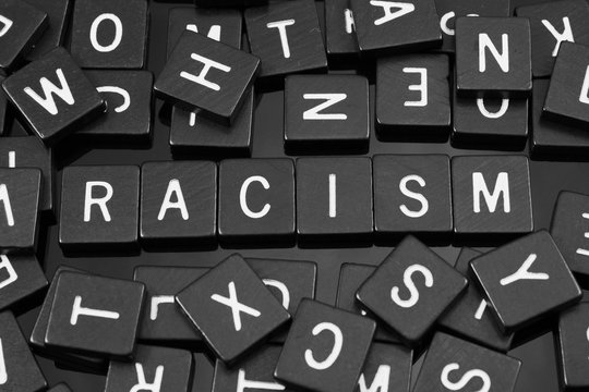 """Black letter tiles spelling the word """"racism"""" on a reflective background"""