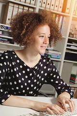 jeune femme rousse stagiaire travaillant dans un bureau en souriant