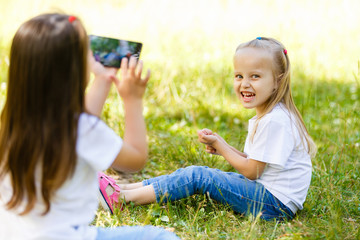 Little girl makes photos of her sister with smartphone outdoors.