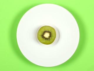 киви фрукт лежит на белой тарелке на зелёном фоне