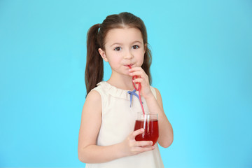 Cute little girl drinking juice on color background