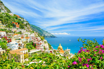 beautiful view on Positano on Amalfi coast with blurred flowers on foreground
