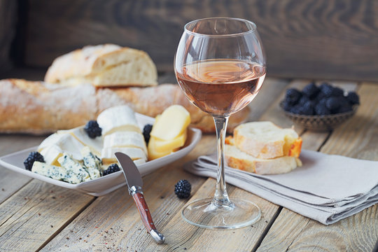A glass of rose wine served with cheese plate, blackberries and baguette