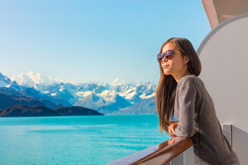 Luxury travel Alaska cruise holiday woman relaxing on balcony looking at view of mountains and nature landscape. Asian girl sunglasses tourist.