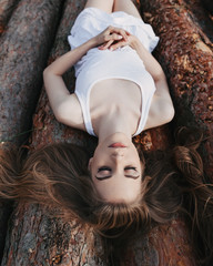 Girl with closed eyes lies on logs