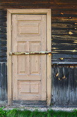 Wooden door of the old rural broken house.