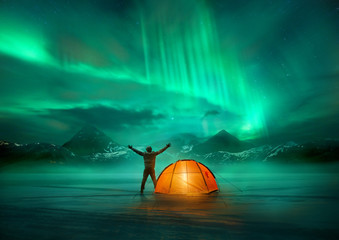 Photo sur Plexiglas Camping A man camping in wild northern mountains with an illuminated tent viewing a spectacular green northern lights aurora display. Photo composition.