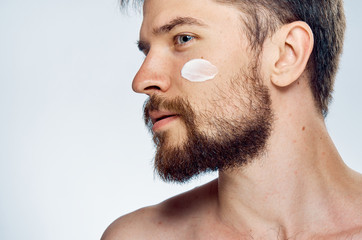 Young guy with beard on white isolated background, face cream