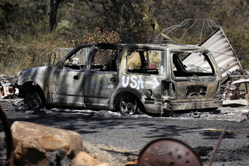 A car burned by the Wall Fire is seen on a property near Oroville