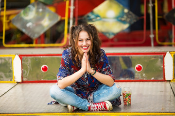 Young woman in the amusement park sitting,smiling and looking in to a camera