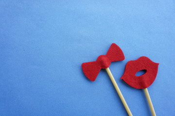 Top or flat lay view of Photo booth props a red lips and a red bow tie on a blue background flat lay. Birthday parties and weddings.