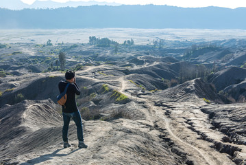 Man on top of Layer Volcanic ash as sand ground of Mount Bromo volcano (Gunung Bromo) at Bromo Tengger Semeru National Park, East Java, Indonesia