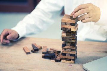 Closeup of businessman making a structure with wooden cubes.