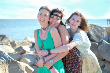 Three happy young hippie girlfriends having fun at the beach