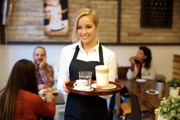 Happy waitress holding tray