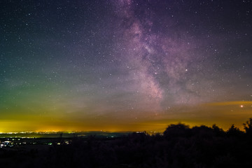 Landscape with the Milky Way as seen from the summit of the mountain Katzenbuckel in the Odenwald in Germany.