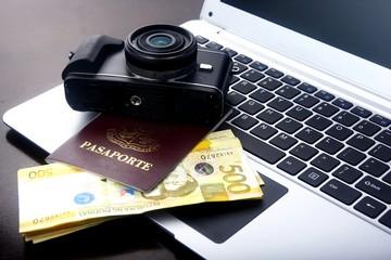 Camera, passport and Philippine peso bills on a laptop computer.