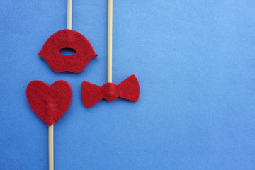 Top or flat lay view of Photo booth props a red heart shape and red bow tie shape on a wooden background flat lay. Birthday parties and weddings.