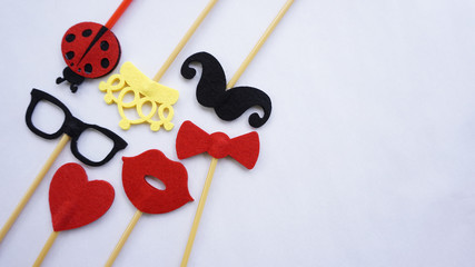 Top or flat lay view of Photo booth props a black mustache a black glases, a red bow tie, a ladybird, a red heart shape, a red lips and a yellow crown on a white isolated background flat lay. Birthday