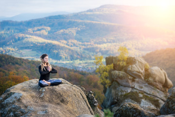Pretty young woman is practicing yoga and doing asana Siddhasana on the top of the mountain in the evening. Autumn forests, rocks and hills on the background