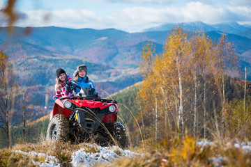 Beautiful females riding on red quad bike in winter clothing on snowy hills on the background of mighty mountains and trees with yellow leaves