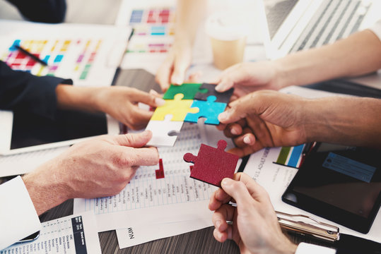 Team of businessmen work together to build a puzzle. Concept of unity and partnership