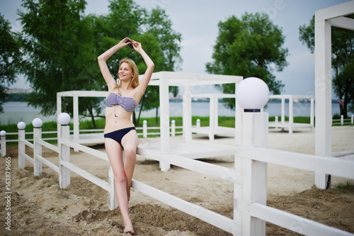 b5a69f93fa Portrait of a stunning young female model in bikini posing next to the white  wooden fence in the park.
