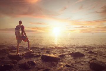 Junger Mann mit Rucksack am Meer bei untergehender Sonne