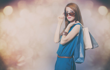 portrait of beautiful young woman with shopping bags on the wonderful grey studio background